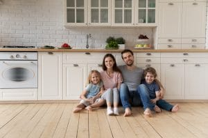 Portrait of happy young family sitting on wooden floor in the kitchen with children.