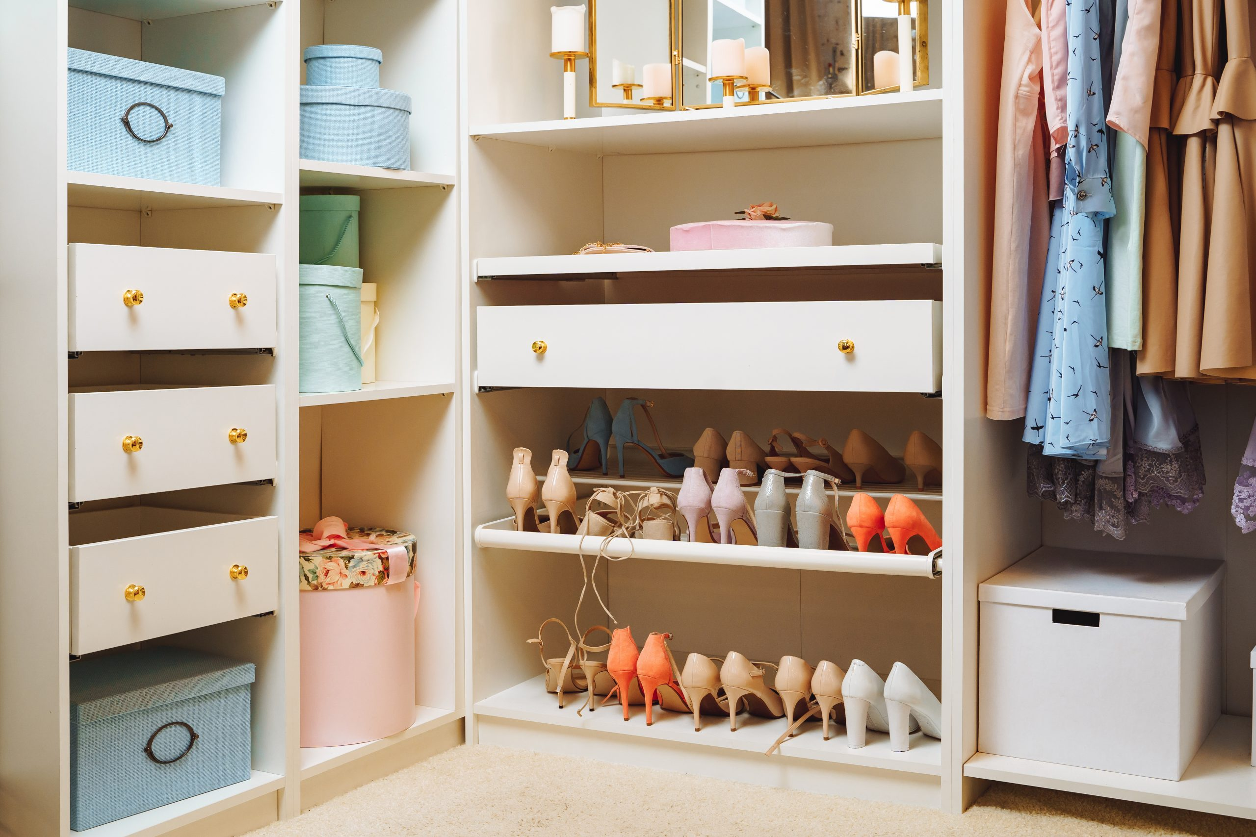 Large wardrobe with stylish women's clothing, shoes, accessories and boxes. Organization of storage space and fashion concept.
