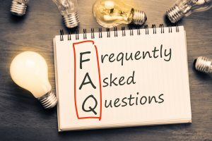 FAQ ( frequently asked questions ) text on notebook with many light bulbs